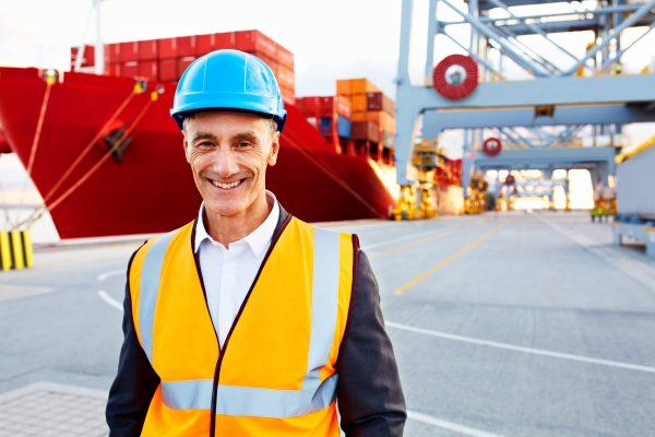 Mann steht vor einem Schiff und denkt über die Möglichkeiten einer Einkaufsfinanzierung nach.