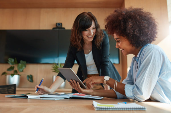 Zwei junge Unternehmerinnen sitzen an einem Arbeitstisch und diskutieren verschiedene Firmenkredite.