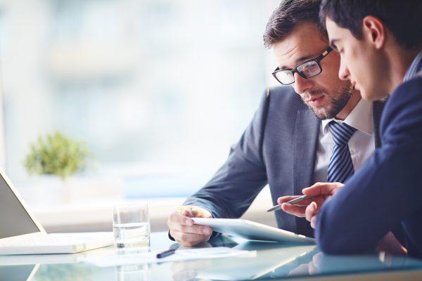 Zwei Unternehmer schauen gemeinsam ein Dokument bezüglich eines Investitionskredits an.
