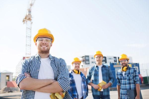 Vier Bauarbeiter mit gelben Helm vor einer Baustelle finanziert durch Einzelforderungsverkauf