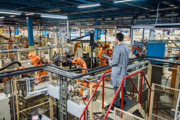 Ingeneur überwacht Flotte von Robotern in einer Produktionsstätte