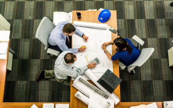Team aus Vogelperspektive sitzt zur Besprechung am Schreibtisch