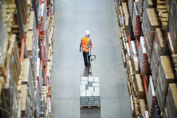 Factorable Ware wird von einem Mitarbeiter durch einen Gang transportiert.