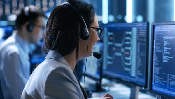 Mitarbeiterin einer IT-Leasing-Gesellschaft sitzt vor mit dem Rücken zur Kamera gekehrt vor ihrem Bildschirm.