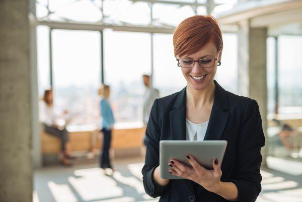 Unternehmerin schaut lächelnd auf ihr Tablet, welches den Vertrag der gerade neu erworbenen Wohnimmobilie beinhaltet.