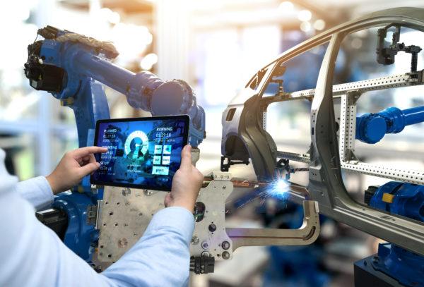 Ingenieur verwendet Tablet um Produktion von Autoteilen zu beobachten