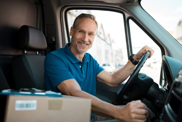 Paketlieferant, der über E-Commerce bestellte Waren mit seinem Lieferwagen zustellt.