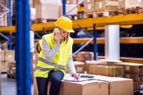 Telefonierende Frau, die Waren- und Logistikfinanzierung beansprucht.