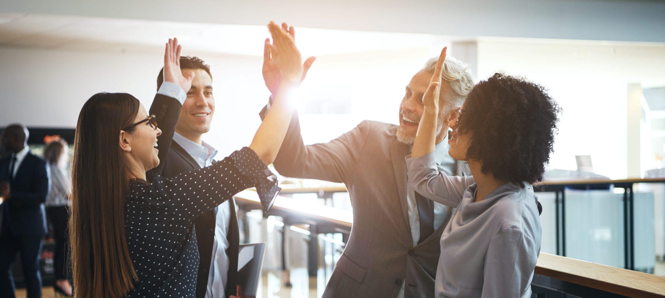 Lächelnde Kollegen geben sich hi five, um sich für Ihren Erfolg zu beglückwünschen.