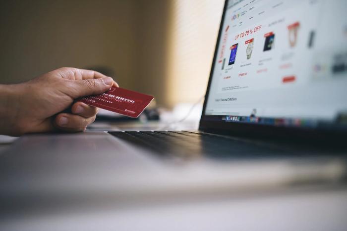 Person hält Kreditkarte in der Hand und Laptop steht auf dem Tisch