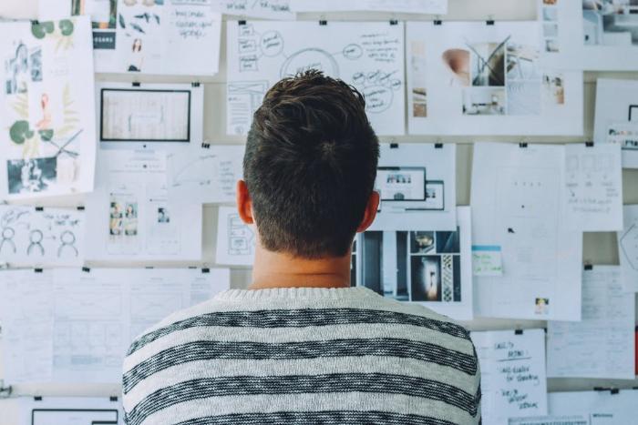 Mann mit dem Rücken zugewendet schaut Wand mit aufgehängden Statistiken und Informationen an