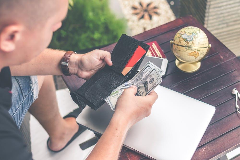 Mann nimmt Geld aus seiner Brieftasche